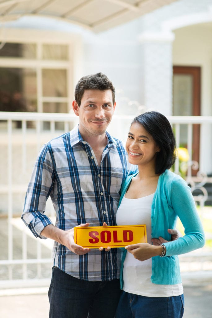Young multiracial couple holding sold-sign